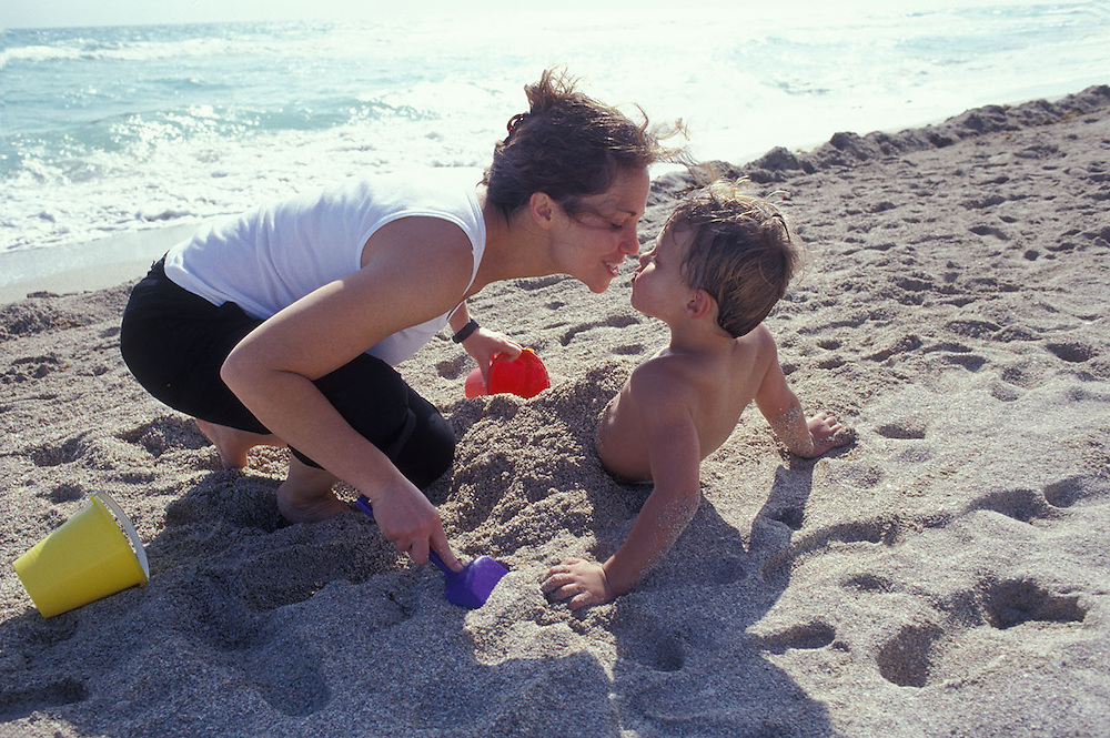 Mother with young boy playing in sand on beach.