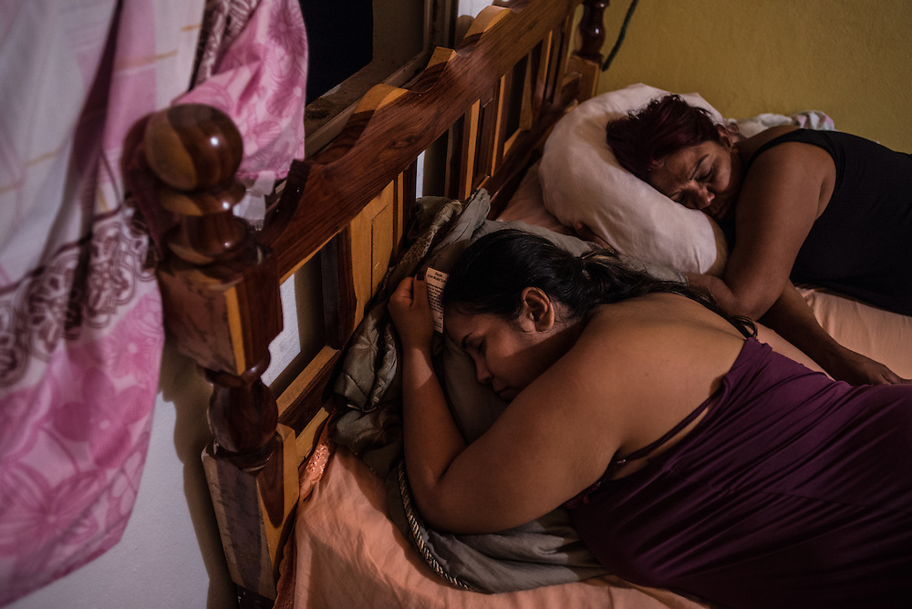 FALCÓN, VENEZUELA - SEPTEMBER 25, 2016: Maria Piñero and Irene Poza spend the night at the safe house while they wait for the smuggler's boat to arrive that will illegally take them from Venezuela to Curaçao. Undocumented migrants here have mortgaged property, sold kitchen appliances and even borrowed money from the same smuggling rings that pack them on the floorboards alongside drugs and other contraband. The journey to Curaçao takes them on a 60-mile crossing filled with backbreaking swells, gangs of armed boatmen and coast guard vessels looking to capture migrants and send them home. Then, after being tossed overboard and left to swim ashore, they hide in the brush to meet contacts who spirit them anew into the tourist economy of this Caribbean island. They clean the floors of restaurants, work in construction, sell trinkets on the street, or even solicit Dutch tourists for sex. But at least, the migrants say, there is food. PHOTO: Meridith Kohut for The New York Times