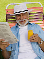 Senior Man in Lawn Chair with Newspaper and Orange Juice