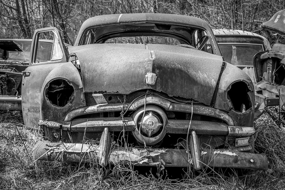 Shot at a low angle with a wide angle lens, this rusted out 1950 Ford sedan appears as sullen old skull in a graveyard. This is one of my favorite images in this gallery. Post processing to emulate black & white film in Alien Skin's Exposure adds the right amount of extra contrast and film grain structure.