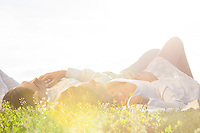 Young couple lying on grass against clear sky