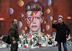 © Licensed to London News Pictures. 10/01/2017. London, UK. Fans gather at a mural and shrine to David Bowie in Brixton. David Bowie who died a year ago today, was born in Brixton, south London. Photo credit: Peter Macdiarmid/LNP