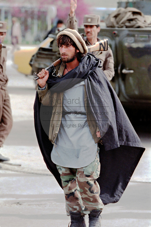 An Afghan mujahideen fighter with Jamayat-E-Islami with Afghan National Army soldiers who have joined with the mujahideen during fighting against Hezb-i Islami forces following the fall of the capital April 19, 1992 in Kabul, Afghanistan. Fighting between mujahideen factions began almost immediately after they captured the city.