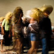 Indigenous men originally from Oaxaca, Mexico and now living in Los Angeles, Calif., dance at a Oaxacan community gathering at a private residence in South Los Angeles, Calif., on August 11, 2007.  The men are dressed in costumes as both men and women, all wearing masks, wigs, and Western dress. The dance was performed both to entertain the gathered crowd -most of whom were members from several Oaxacan-American organizations-and to make a somber and mocking statement about Indigenous Oaxacans who come to the United States, and who loose touch with their indigenous roots and culture by assuming Western practices, such as women who dye their hair blonde, or men who flaunt excessive, street gangster-style jewelry.  Photo by Jen Klewitz