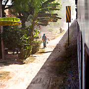 A train passes by a small village in India. I shot this leaning out the door of the train.