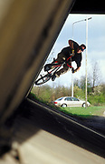 BMX rider, James Hitchcox, doing tricks under a motorway flyover. UK 1990's