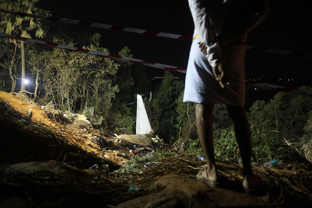 An onlooker watches the airline crash site after rescue operations are concluded for the day,  on May 22, 2010 in Mangalore. An Air India Express Dubai-Mumbai Boeing 737-800 series aircraft overshot the runway on arrival and crashed into a forest. Airline officials say 8 people have been rescued while nearly 160 others are feared dead. (Photo by Prashanth Vishwanathan/Getty Images)