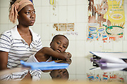Dr. Denise Mobio (not seen) meets with Kadidiatou Sy, 27, and her son Junior Karampire, 5, who suffers from recurring ear infections, at the Koumassi General Hospital in Abidjan, Cote d'Ivoire on Friday July 19, 2013.