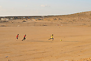 Israel, Negev, Bedouin children play football in a sand playground