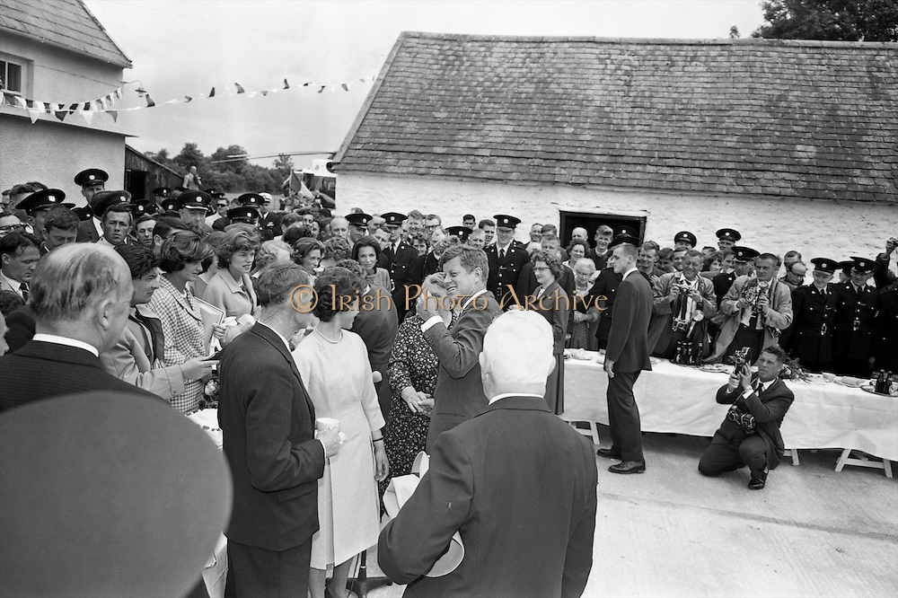 Kennedy in Ireland.  President Kennedy visits the homestead of his great-grandfather at Dunganstown, Co. Wexford and drinks a cup of tea with the present owner of the cottage, a second cousin of the President, Mrs. Mary Ryan (neé Kennedy)..26.06.1963