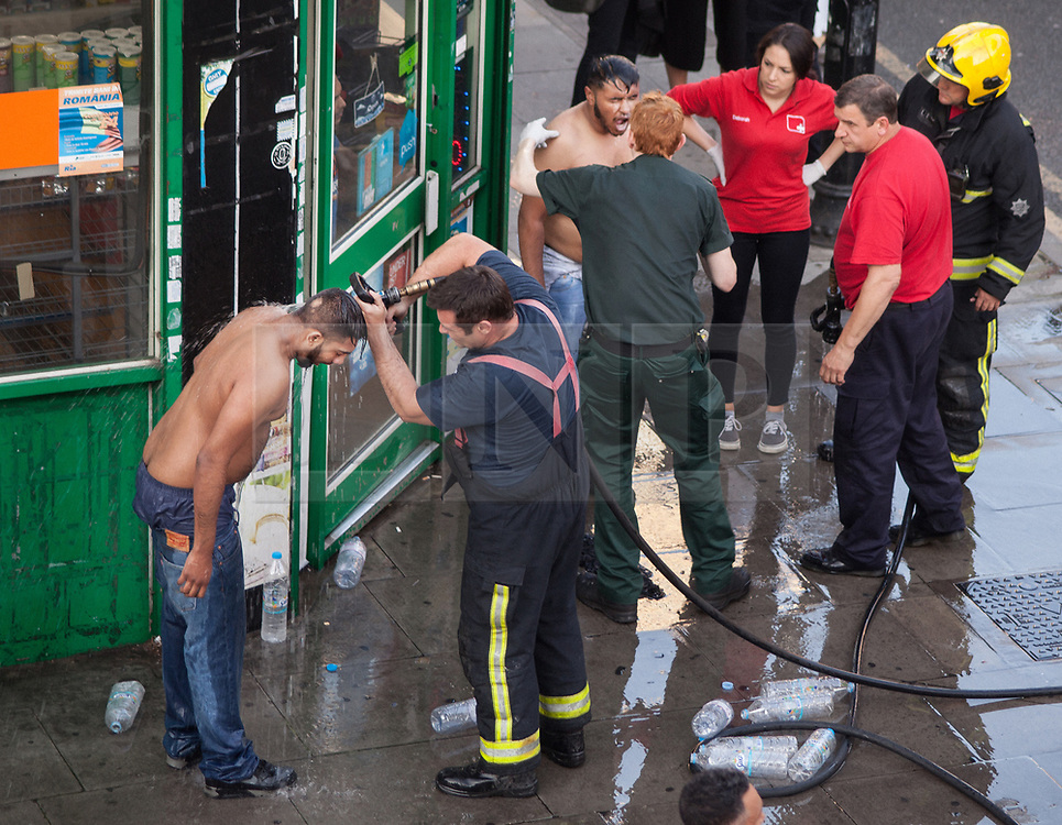 © Licensed to London News Pictures. 25/07/2017. London, UK. Two victims of what is thought to have been an acid attack have water poured on their heads by a firemen - on the side of the road in Bethnal Green. Two men have been taken to hospital after flagging down police for help. Photo credit: Liam Creighton/LNP