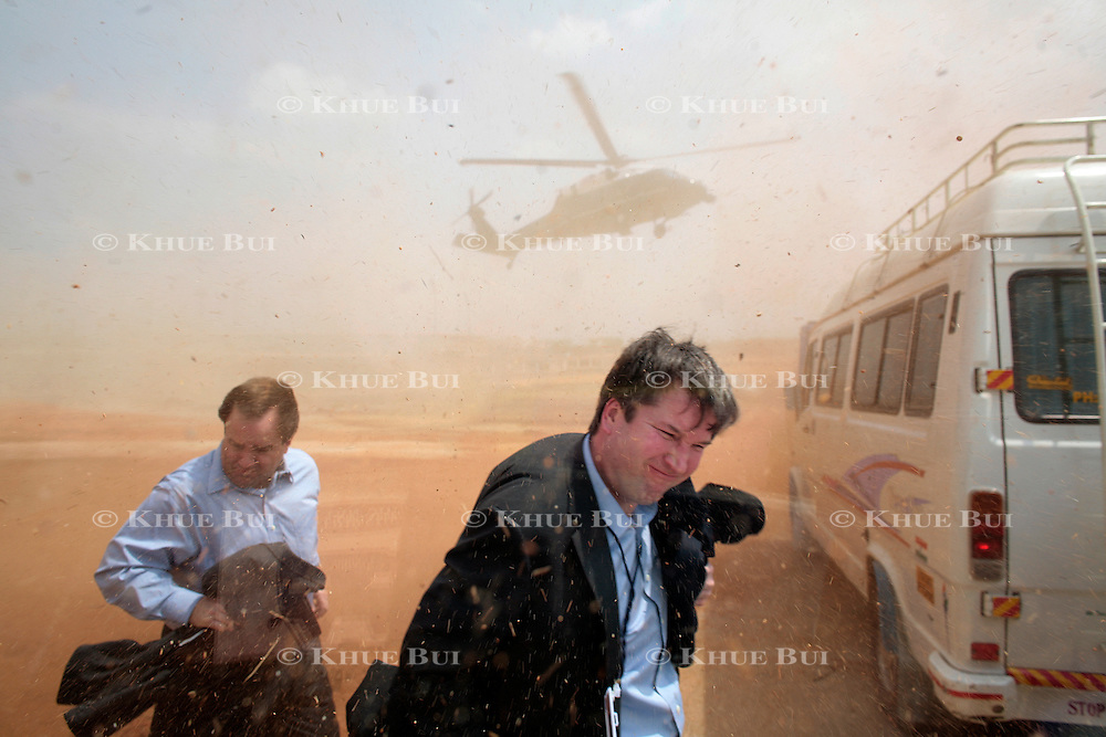 White House Staff Secretary Brett Kavanaugh and Press Secretary Scott McClellan run for cover as a sandstorm created by a landing Marine One envelopes them Friday, March 3, 2006, in Hyderabad, India...Photo by Khue Bui