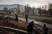Construction along the Northern river bank of the Ibar river by a small team of Albanian workers.