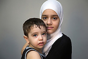 Syrian refugee Nahid (age 12) holds her brother Gais (age 2) during a CARITAS Egypt authorized home visit in Obour, Egypt September 23, 2016. Photo by UNHCR/Scott Nelson