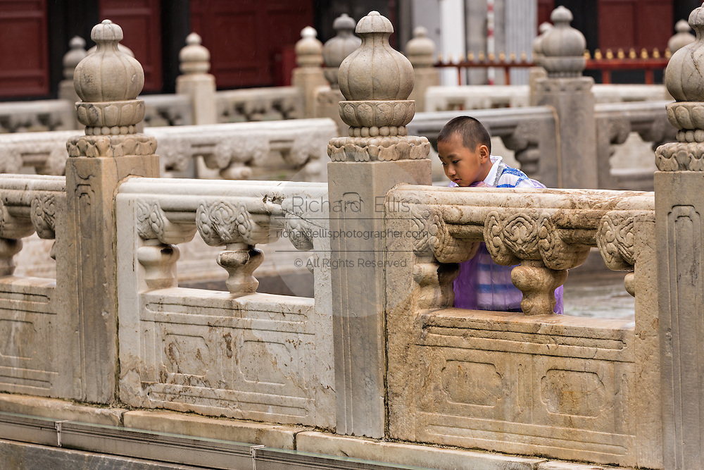A young boy looks at koi carp at the Temple of Confucius in Beijing, China