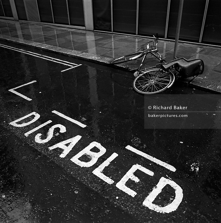 This black and white scene is in a City of London side street where a bicycle parked on a parking pole at a kerbside has somehow fallen over in the gutter. Fittingly, the parking bay is for specifically for a disabled motorist and that word has been stencilled in bold white lettering on the wet road surface after a rain shower. The pavement and tarmac glisten making it slippery but the bike has been left and there is no-one in this scene. Reflected inn the puddle is the modern architecture of the office building, also seen rising from street level.