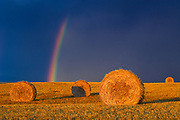 Bales and rainbow after storm at sunset<br />