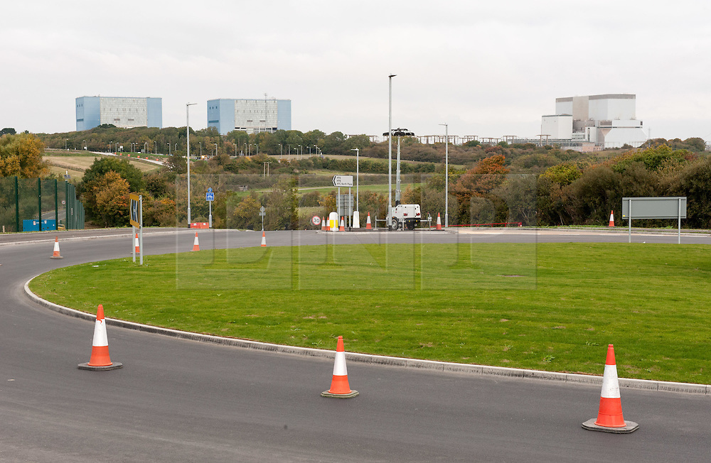 "© Licensed to London News Pictures. 19/10/2015. Hinkley Point, Somerset, UK.  View towards the existing Hinkley Point nuclear site, with Hinkley A (left) being decommissioned, and Hinkley B (right) still operating. Anti-nuclear protest by the ""Osborne's Folly"" (after the Chancellor George Osborne) group, protesting against the proposed new nuclear power station Hinkley C and against Chinese investment in the project.  The group has occupied a roundabout near the site and erected an inflatable white elephant with a banner written in Chinese and say they want to send a message to the visiting Chinese President Xi Jinping that EDF's Hinkley C would be ""a bad investment"" for the Chinese state. They say that the stalled project has become ""Osborne's Energy Folly"" and should now be abandoned.  Theo Simon, one of the campaigners said: """"Ironically, the Chinese are leading the world in renewable energy investment in their own country, where there is also a growing anti-nuclear movement"". Photo credit : Simon Chapman/LNP"