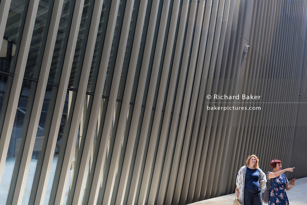 Beneath new architecture, two ladies walk along Bevis Marks in the City of London, the capital's financial district, on 17th June 2019, in London, England.