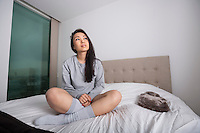 Full length of thoughtful young woman sitting on bed