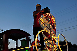 Dennis Miller makes some last-minute adjustments to his Salinas Host Lions entry before Sunday night's 2013 Holiday Parade of Lights along Main Street in Salinas.