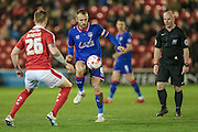 Liam Kelly (Captain) (Oldham Atheltic) controls the ball while Alfie Mawson (Barnsley) and Simon Hooper (referee) watch on during the Sky Bet League 1 match between Barnsley and Oldham Athletic at Oakwell, Barnsley, England on 12 April 2016. Photo by Mark P Doherty.