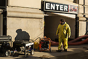 A worker at 30 West St, wearing clothing oil-soaked from working in the flooded parking garage behind him. The tide mark from the floodwaters can be seen on the wall, above the shadow of his head.