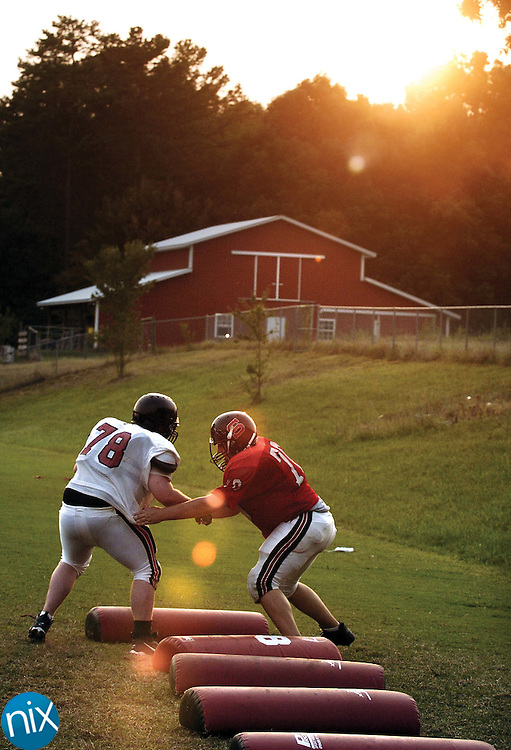 David Archie, left, and Adam Mann run through drills as the sun sets during the South Rowan High football team's practice Tuesday Aug. 14. Because of the heat, area teams are starting practice later in the evening, some practices going as late as 9 p.m.