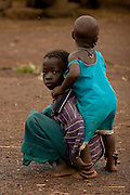 A girl takes care of a younger child in the village of Nyologu, northern Ghana, on Wednesday June 6, 2007.