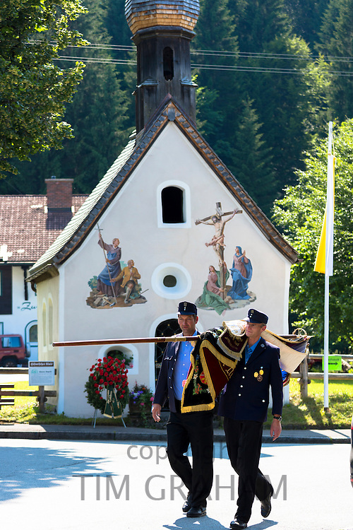 Soldiers carry ceremonial flag past Church of St Peter and Paul in the village of Klais in Bavaria, Germany