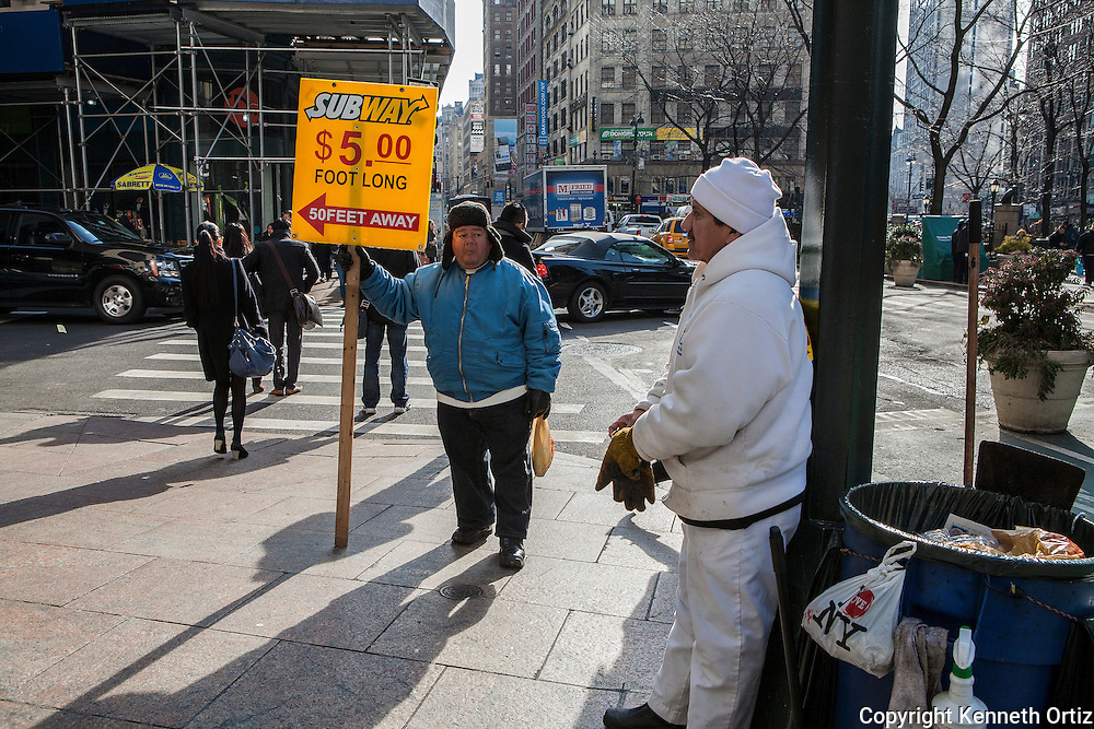 A man holding a sign with a Subway logo advising people where the fast food restaurant is, looks toward another street worker who Leans against a pole and knows that his day of picking up garbage is not over soon enough.