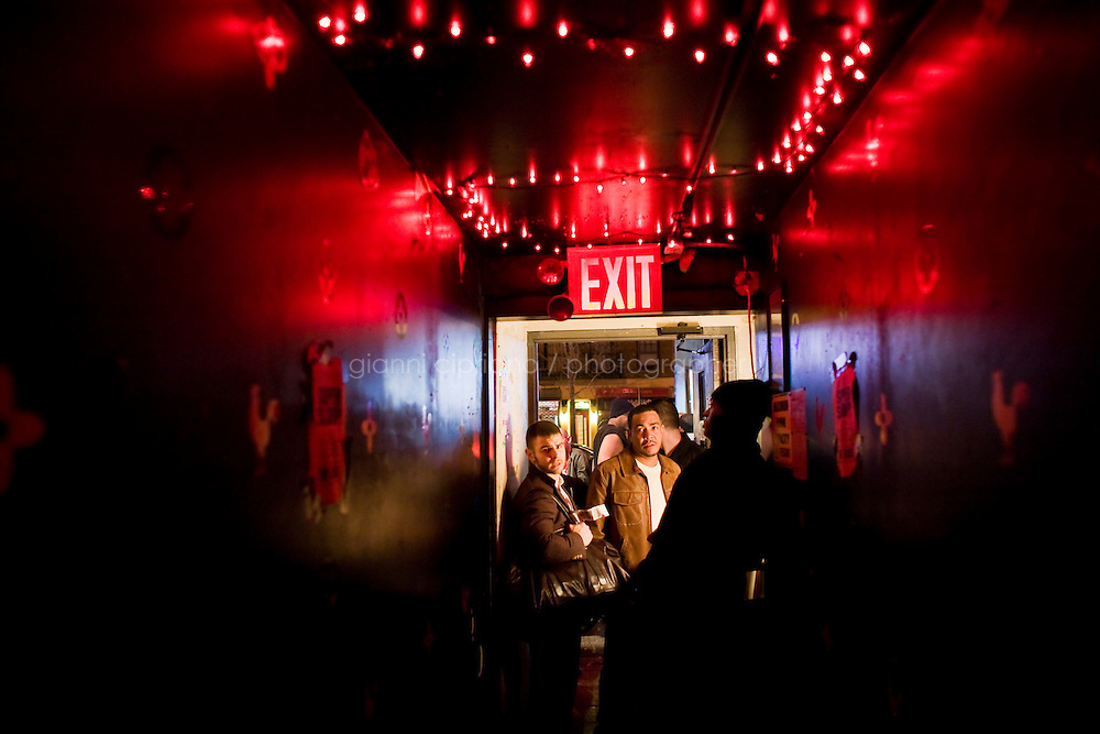 11 December, 2008. New York, NY. Daniel Alexander Osach (or Dan Alex), 24, exits The Cock Bar in East Village after his performance as a Go-Go dancer. Daniel is a gay Go-Go dancer who grew up in New Haven, CT, and moved to New York a year ago. During the day he works for Christopher Hyland, Inc., a high-end fabrics purveyor. At night, he works as a Go-Go dancer in gay and women clubs around New York City. &quot;My life is work, gym, dance and sleep&quot;, Daniela says. Dan has a bachelor in English and majored in Poetry and Economics. After graduation in 2006 he worked as a store manager in a mall for 4 months in Connecticut. Tired and depressed of his job, he went to Florida to relax and then came to New York a year ago. He usually dances at &quot;The Cock&quot;, a  East Village gay bar. &quot;The Cock is not an institution. It's a landmark&quot; Daniel says. Daniel aspires to become maybe a teacher or to work for a travel magazine. &quot;What I would really love to do is to live my life laying down at the beach and reading poetry&quot;<br /> <br /> &copy;2008 Gianni Cipriano for The New York Times<br /> cell. +1 646 465 2168 (USA)<br /> cell. +1 328 567 7923 (Italy)<br /> gianni@giannicipriano.com<br /> www.giannicipriano.com
