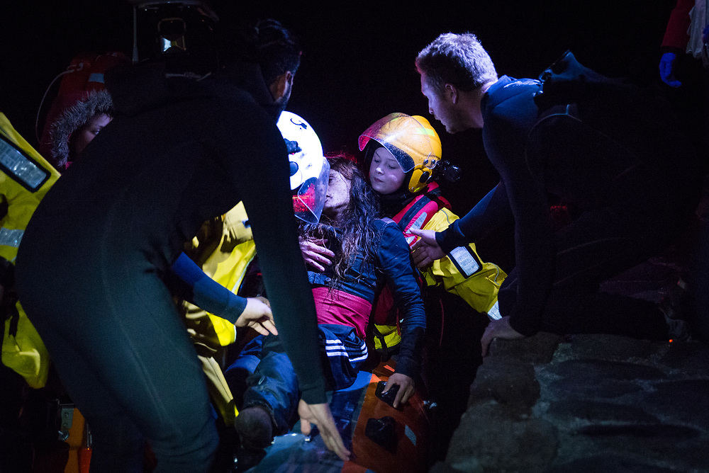Rescue workers lift an Afghan woman out of a boat shortly after being rescued at sea off the north shore of Lesvos, Greece, on March 2, 2017. 45 refugees were saved when the rubber boat they were travelling in began to sink during the crossing from Turkey to Greece.<br />