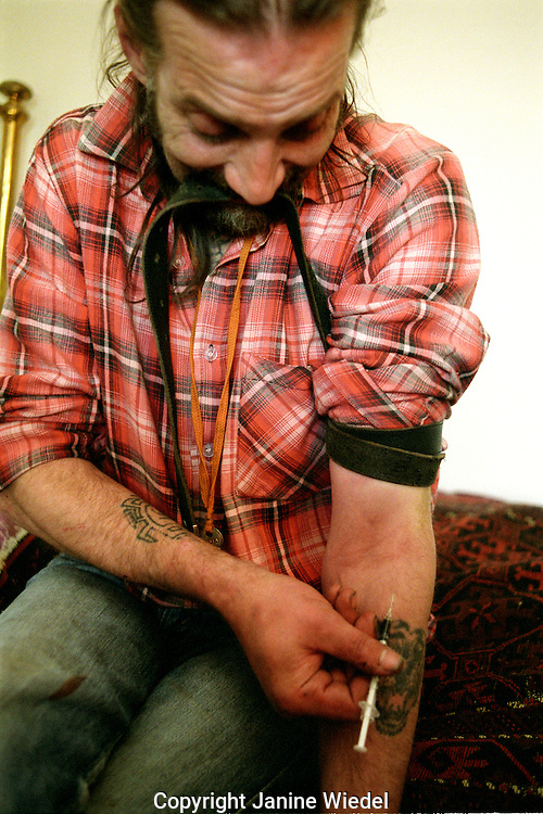 Heroin addict in his bedroom injecting  into his arm.