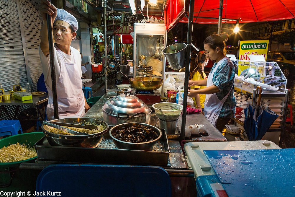 18 SEPTEMBER 2013 - BANGKOK, THAILAND: A street food stall chef relaxes while he waits for customers in the Chinatown section of Bangkok. Thailand in general, and Bangkok in particular, has a vibrant tradition of street food and eating on the run. In recent years, Bangkok's street food has become something of an international landmark and is being written about in glossy travel magazines and in the pages of the New York Times.      PHOTO BY JACK KURTZ