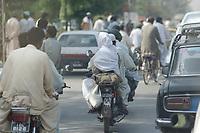 19 OCT 2001, ISLAMABAD/PAKISTAN:<br /> Mopedfahrer auf einer Hauptstrasse von Islamabad<br /> IMAGE: 20011019-02-044<br /> KEYWORDS: Motorrad, Motorradfahrer, motorbike, Kopftuch, Schleier