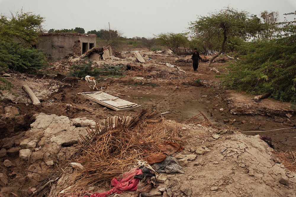 Residents walk through the remains of their destroyed village of Geo Kaloid in Mirpur Khas district, Sindh, Pakistan on November 3, 2011. The village was completely destroyed in recent floods and residents are living in makeshift shelters alongside a nearby road. 1.5 inches of rain receding each day an it will take 4-6 months to drain all the water and begin to rebuild homes. The villagers have no savings to reconstruct their homes. It costs 80-100,000 to rebuild a decent house.  The village is made up of farmers and labourers..In August 2011, Heavy monsoon rains triggered flooding in lower parts of Sindh and northern parts of Punjab.