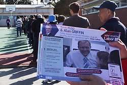 © Licensed to London News Pictures. 7/9/2013. Labour party volunteers holds up a Labour party how to vote card in front of a queue of Voters during the Australian Federal Election. Photo credit : Asanka Brendon Ratnayake/LNP