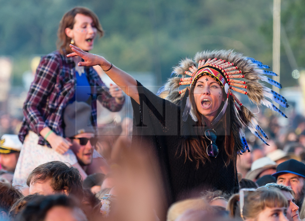 © Licensed to London News Pictures. 13/06/2015. Isle of Wight, UK.  Festival goers dance on friends shoulders watching Pharrell Williams perform at Isle of Wight Festival 2015 on Saturday Day 3.  Yesterday suffered torrential rain all afternoon and evening, after a first day of warm sun.  This years festival include headline artists the Prodigy, Blur and Fleetwood Mac.  Photo credit : Richard Isaac/LNP