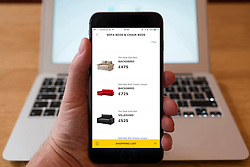 Using iPhone smartphone to display sofas for sale in IKEA online home furnishing superstore