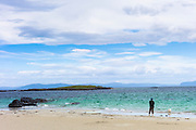 Lone person with dog on shoreline of sandy beach looking out to turquoise sea on Isle of Iona in the Inner Hebrides and Western Isles, Scotland