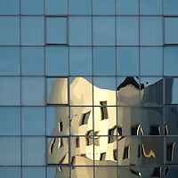 The irregular reflection of a modern building in a mirror window facade.