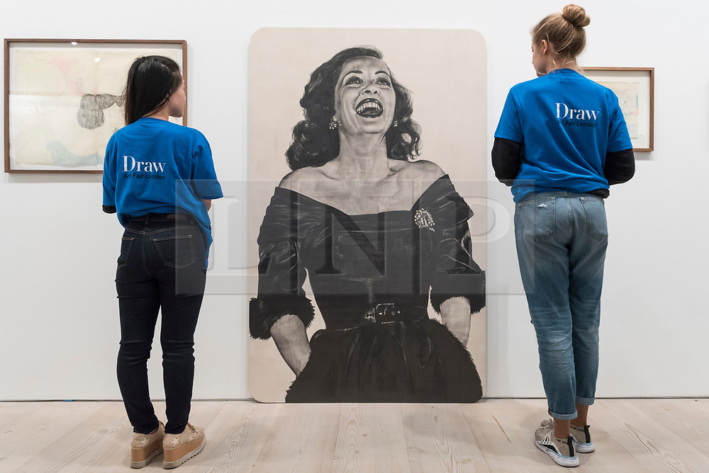 "© Licensed to London News Pictures. 17/05/2019. LONDON, UK. Staff members view ""Bette"", 2018, by Nina Mae Fowler (GBP9,000) at the Draw Art Fair London, the first fair in the UK dedicated to modern and contemporary drawing.  58 international galleries have juxtaposed drawings with related paintings, sculptures, photos or videos, in a ratio of approximately 70% to 30%, using drawing as the core concept.  The inaugural show is open to the public 17 to 19 May 2019 at the Saatchi Gallery in Chelsea.  Photo credit: Stephen Chung/LNP"
