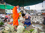 09 OCTOBER 2012 - BANGKOK, THAILAND:  A Buddhist monk collects alms from a produce vendor near the Bangkok Flower Market. Most males in Thailand enter the Sangha (become Buddhist monks) at least once in their lives. Their time in the Sangha may be as short as a few weeks or as long as a lifetime commitment. The Bangkok Flower Market (Pak Klong Talad) is the biggest wholesale and retail fresh flower market in Bangkok. It is also one of the largest fresh fruit and produce markets in the city. The market is located in the old part of the city, south of Wat Po (Temple of the Reclining Buddha) and the Grand Palace.    PHOTO BY JACK KURTZ