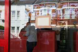 © Licensed to London News Pictures. 19/04/2019. London, UK. The gun shots on Tasty Chicken's front window boarded up. A 16 year old was shot just before 10 pm on Thursday 18 April 2019 outside Tasty Chicken on Burfield Close in Tooting. The victim is in a life threatening condition hospital. Photo credit: Dinendra Haria/LNP