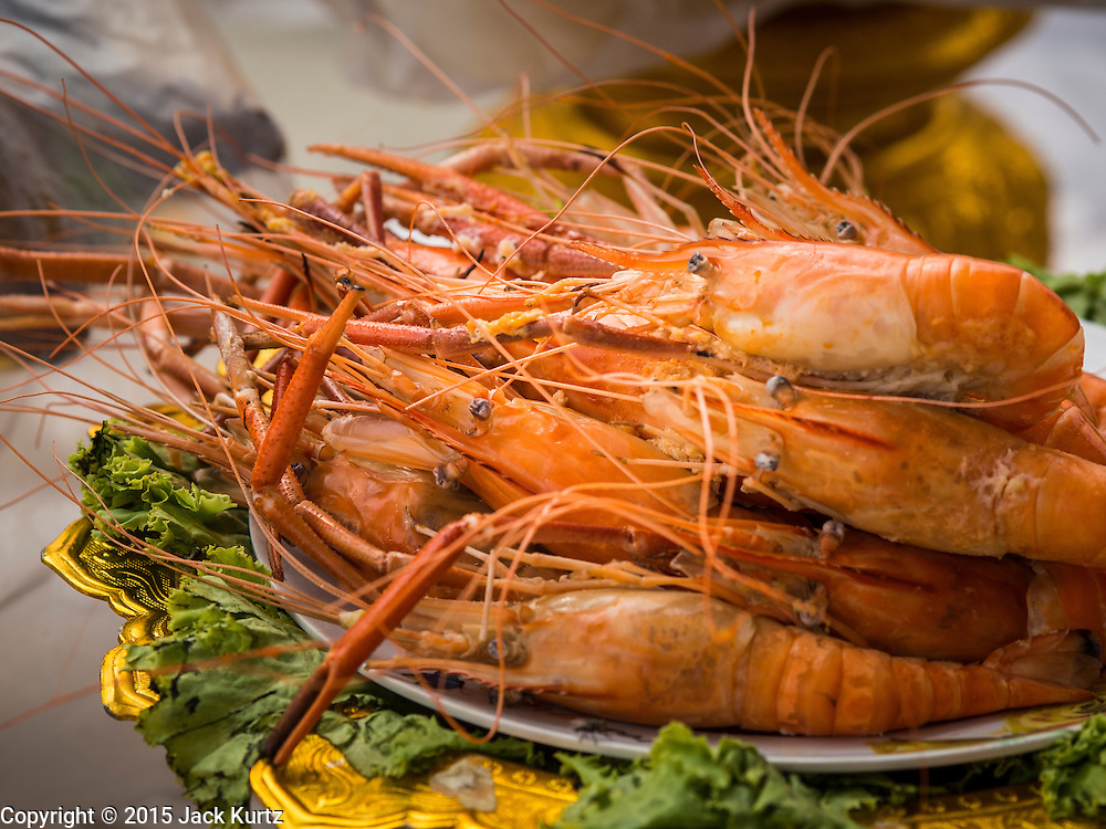12 MARCH 2015 - BANGKOK, THAILAND:  Grilled shrimp left as an offering at the City Pillar Shrine in Bangkok. Bangkok's city pillar shrine (also known as San Lak Muang) is one of the most important city pillar shrines in Thailand. The shrine is in the heart of Bangkok, opposite the grand palace in the southeast corner of the Sanam Luang and close to the Ministry of Defence. The shrine was built after the establishment of the Rattanakosin Kingdom (Bangkok) to replace the old capital of the Thonburi Kingdom during the reign of King Rama I in 1782. It was intended to be the spiritual center for Thai citizens.     PHOTO BY JACK KURTZ