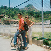 Two boys by a concrete fence one on his bike Brazil