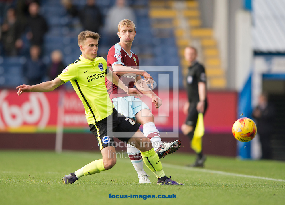 Ben Mee of Burnley (right) plays the ball forward while closed down by Solly March of Brighton and Hove Albion (left) during the Sky Bet Championship match at Turf Moor, Burnley<br /> Picture by Russell Hart/Focus Images Ltd 07791 688 420<br /> 22/11/2015