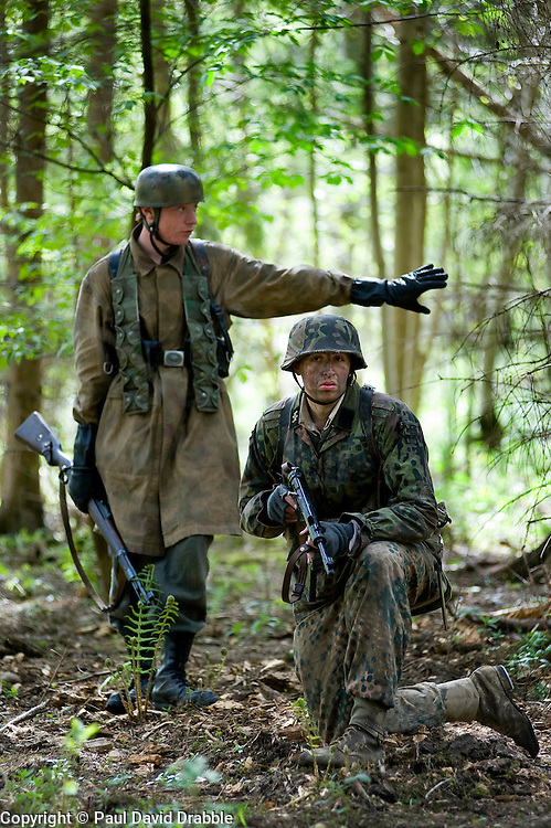 Living History Reenactors a Fallschirmjaeger (German Paratrooper) carrying a Mauser k98 rifle  and a  Waffen SS soldier weraing Pea Dot and Oakleaf camouflage with an MP40 Sub machine gun in a Woodland setting. <br /> Images &copy; Paul David Drabble.