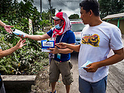 23 JANUARY 2018 - GUINOBATAN: ALBAY, PHILIPPINES: Face masks for protection from an ash fall are handed out in Guinobatan. The Mayon volcano continued to erupt Tuesday, although it was not as active as it was Monday. There were ash falls in communities near the volcano. This is the most active the volcano has been since 2009. Schools in the vicinity of the volcano have been closed and people living in areas affected by ash falls are encouraged to stay indoors, wear a mask and not participate in strenuous activities.    PHOTO BY JACK KURTZ